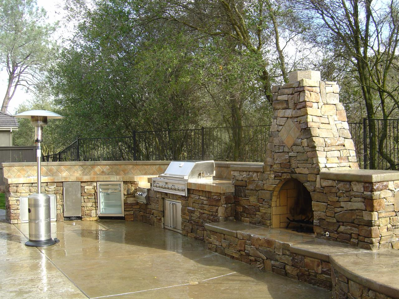 outdoor kitchen and fireplace.  to utilize our kitchens fireplaces and pits all year long Custom design installation insure the right size form for any yard Mayes Landscape Outdoor Kitchens Fireplaces